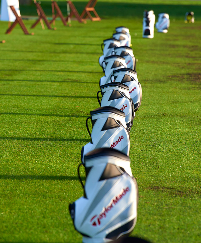 Golf bags lined up at the practice facility